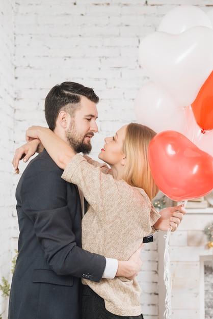 Carinhoso, par, com, balões, em, abraço Foto gratuita