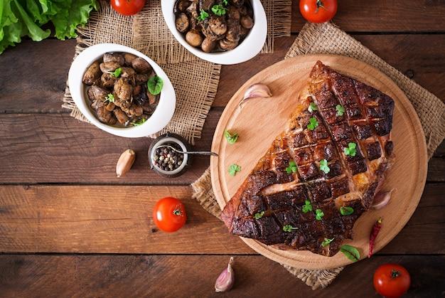 Carne assada com especiarias e alho na mesa de madeira. vista do topo Foto Premium