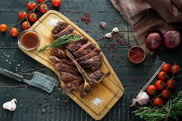 Carne assada em um osso e legumes frescos em uma tábua de madeira em estilo rústico Foto Premium