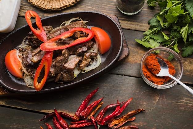 Carne cozida com tomates e pimentos na panela Foto gratuita