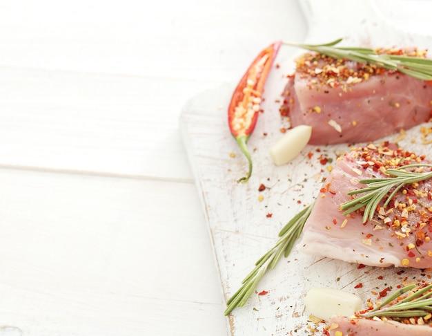 Carne crua com ervas e especiarias em um quadro branco Foto gratuita