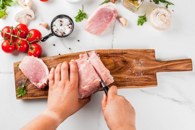 Carne crua com ingredientes para o jantar. pessoa cortar filé de porco, filé, na tábua, com sal, pimenta, salsa, alecrim, óleo, alho, tomate, cogumelo. mesa de pedra preta, cópia espaço Foto Premium