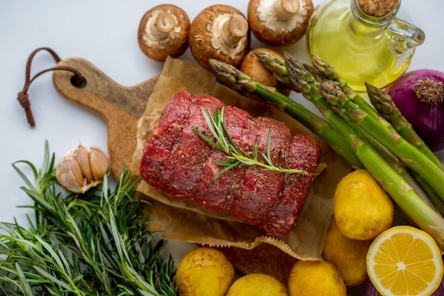 Carne crua de carne vermelha com alecrim verde e legumes frescos em uma tábua de madeira Foto Premium