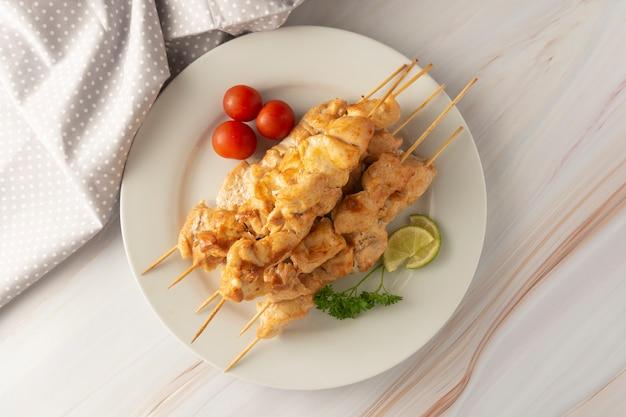 Carne da galinha no no espeto de bambu dos espetos na placa branca, fundo brilhante de mármore. dieta de alimentos com pouca gordura. Foto Premium
