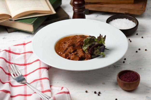 Carne de borrego refogada, guisado em molho de tomate e browh, servido com legumes e sumakh. Foto gratuita