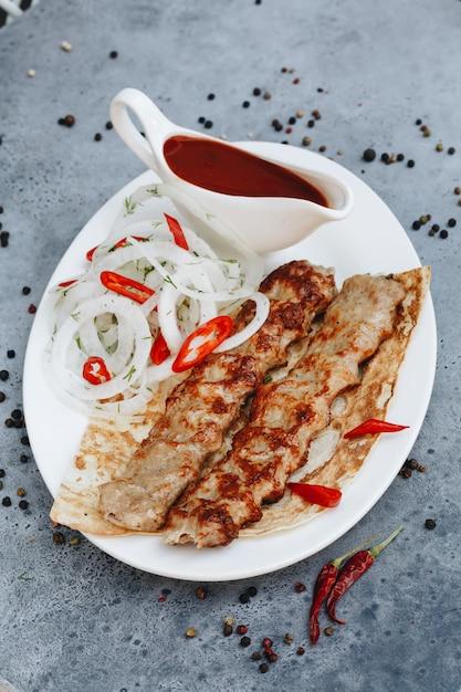 Carne de kebab com ketchup na chapa branca. Foto Premium