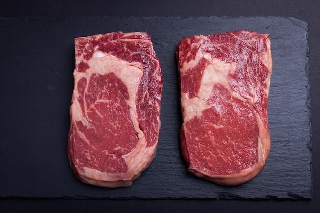 Carne de mármore dois crua, bife preto do ribeye de angus. Foto Premium