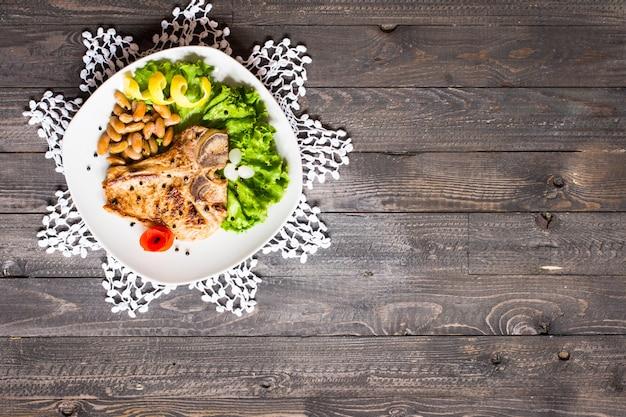 Carne de porco cozida caseira com especiarias folhas de alface na tábua de madeira e um prato, Foto Premium