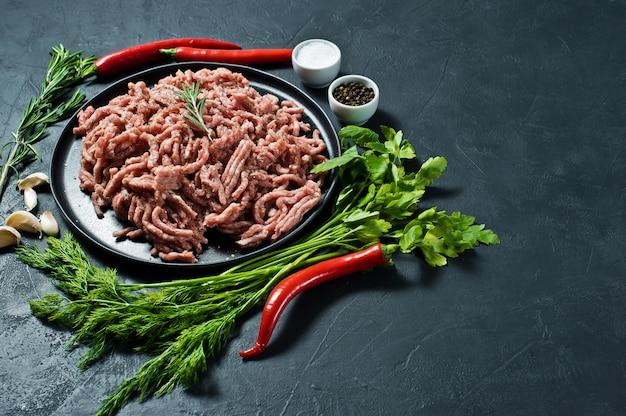 Carne de porco crua triturada em uma placa preta. Foto Premium