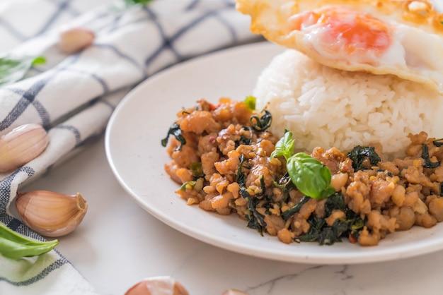 Carne de porco frito com manjericão no arroz e ovo frito Foto Premium