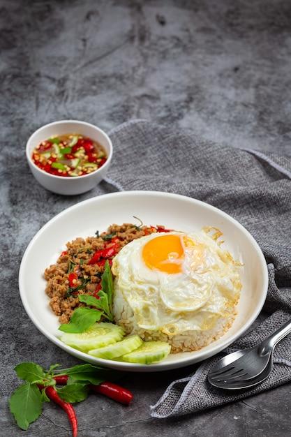 Carne de porco picada com manjericão com arroz e ovo frito Foto gratuita