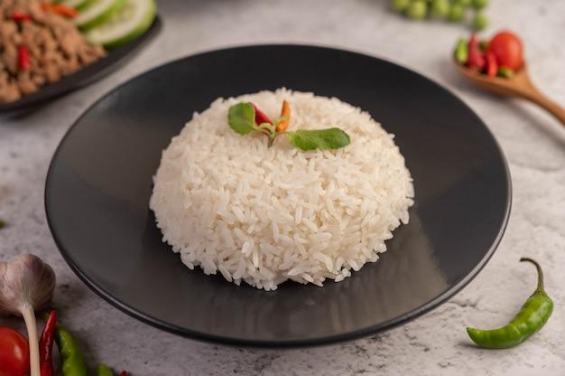 Carne de porco picada e arroz picados em uma placa preta. Foto gratuita