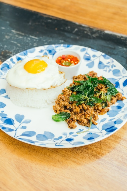 Carne de porco picante com folhas de manjericão e arroz Foto gratuita
