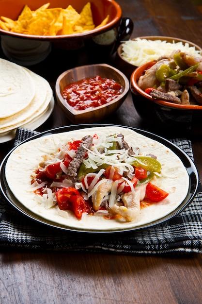 Carne e frango fajitas com pimentões coloridos em tortilla pão e molhos Foto Premium