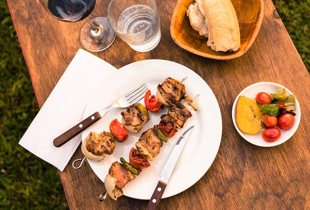 Carne e legumes churrasco servindo na mesa e copo de vinho Foto gratuita