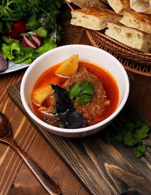 Carne, ensopado de borrego, sopa bosbash com batatas, manjericão e salsa em molho de tomate. Foto gratuita