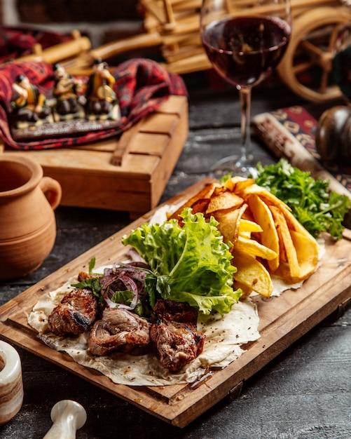 Carne frita com batatas e copo de vinho tinto Foto gratuita