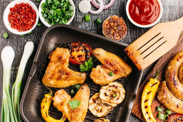Carne frita com legumes e salsicha espiral na mesa de madeira Foto gratuita