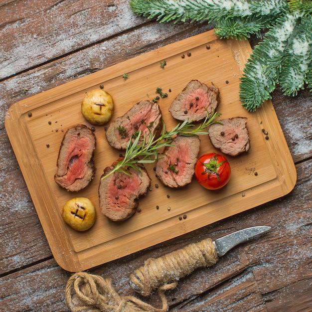 Carne frita com legumes na placa de madeira Foto gratuita