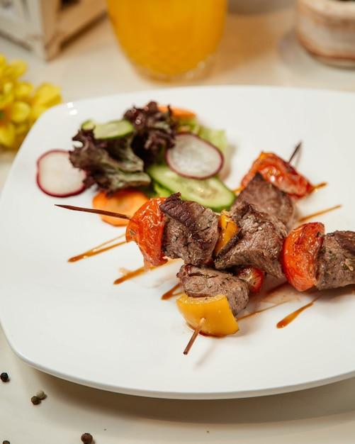 Carne frita e legumes no palito Foto gratuita