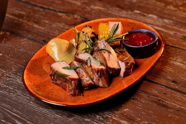 Carne grelhada com milho, molho e um raminho de alecrim. em uma mesa de madeira Foto Premium
