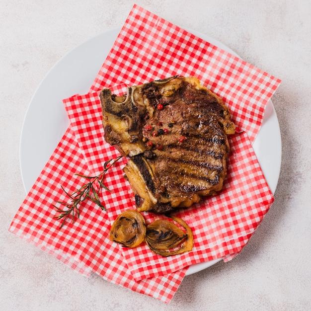 Carne grelhada no prato com toalha xadrez Foto gratuita