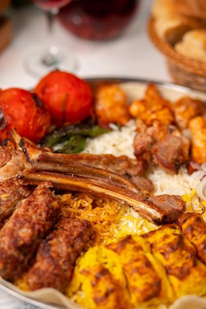 Carne, kebab de frango, churrasco com batatas assadas, grelhadas, tomates e servido com arroz. Foto gratuita