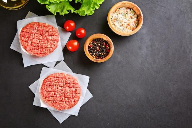Carne picada crua para hambúrgueres de grelhados caseiros cozinhar com espaços e ervas. Foto Premium
