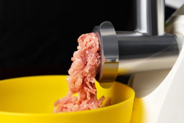 Carne picada em um moedor de carne elétrico Foto gratuita