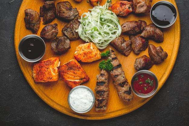 Carnes e molhos grelhados assorted em uma tabela de madeira. Foto Premium
