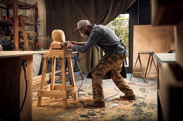 Carpenter viu para cortar escultura de madeira cabeça de um homem Foto Premium