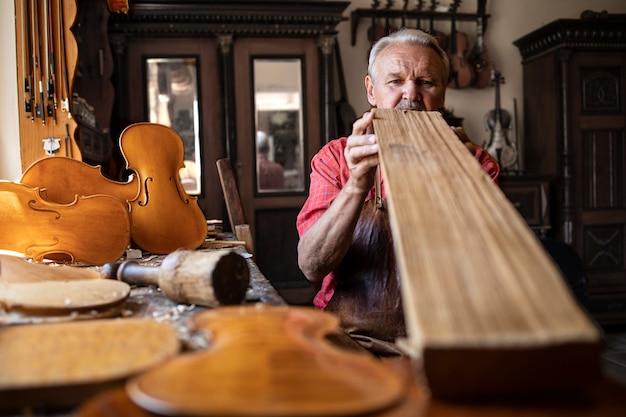 Carpinteiro artesão sênior verificando a qualidade da prancha de madeira antes do trabalho Foto gratuita