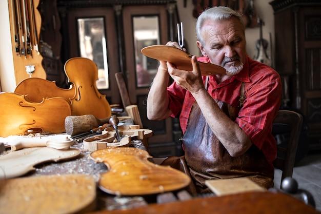 Carpinteiro artesão sênior verificando a qualidade do som do material de madeira em sua oficina de carpinteiro tradicional Foto gratuita