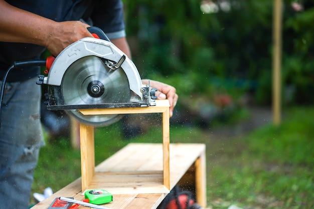 Carpinteiro asiático está a serrar a madeira Foto Premium