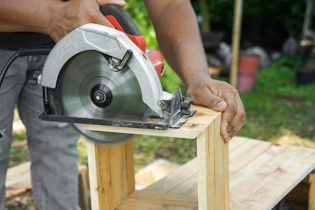 Carpinteiro asiático está serrando a madeira no jardim do quintal de casa. Foto Premium