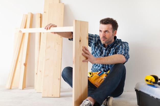 Carpinteiro bonito trabalhando em móveis novos Foto gratuita