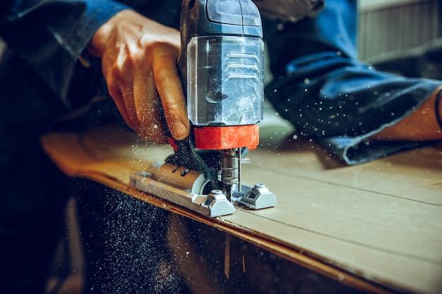 Carpinteiro com serra circular para cortar tábuas de madeira. detalhes de construção de trabalhador masculino ou trabalhador manual com ferramentas elétricas Foto gratuita