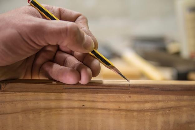 Carpinteiro com um lápis marca a peça de trabalho Foto Premium