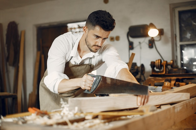 Carpinteiro considerável que trabalha com uma madeira Foto gratuita