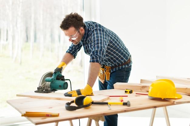 Carpinteiro cortando tábua com serra circular Foto gratuita
