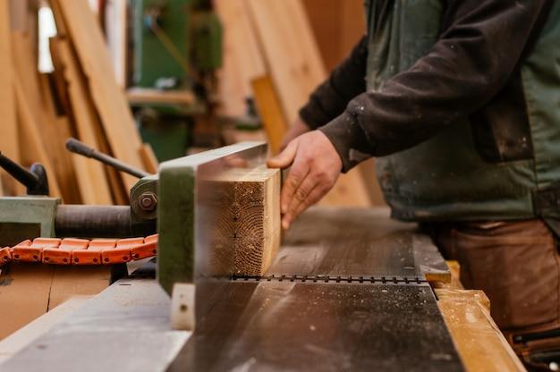 Carpinteiro cortando uma prancha de madeira Foto Premium