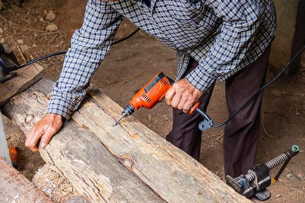 Carpinteiro está trabalhando para perfurar madeira Foto Premium