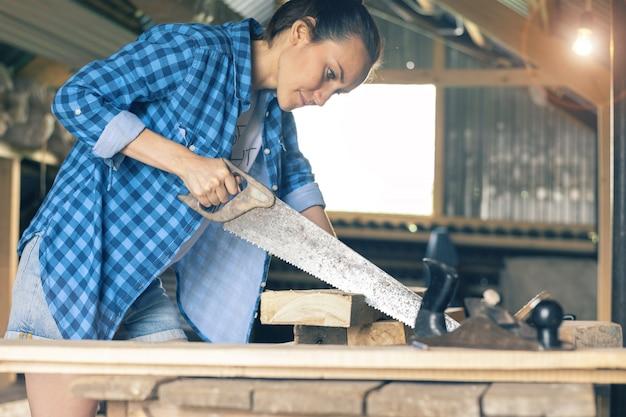Carpinteiro feminino com serra, serrar as placas na oficina Foto Premium