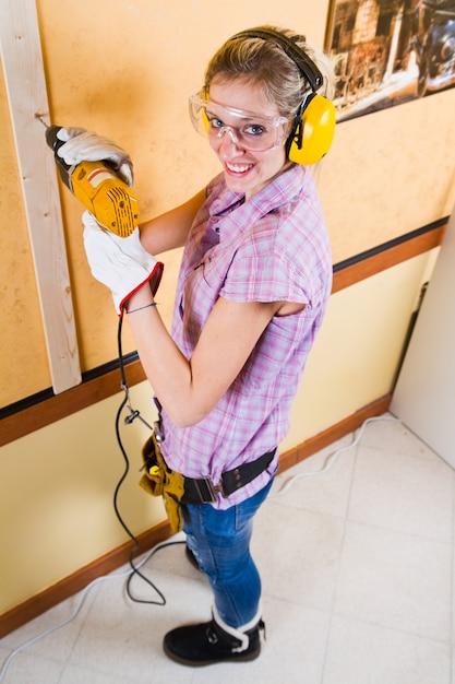 Carpinteiro feminino no trabalho usando a máquina de perfuração de mão Foto Premium