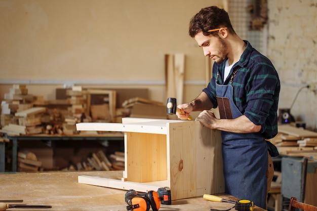 Carpinteiro martelar um prego na placa de madeira Foto Premium