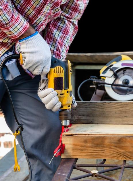 Carpinteiro masculino faz um furo em uma prancha de madeira com uma furadeira elétrica com fio para a junta de topo aparafusada. ferramentas e equipamentos para o conceito de madeira. Foto Premium