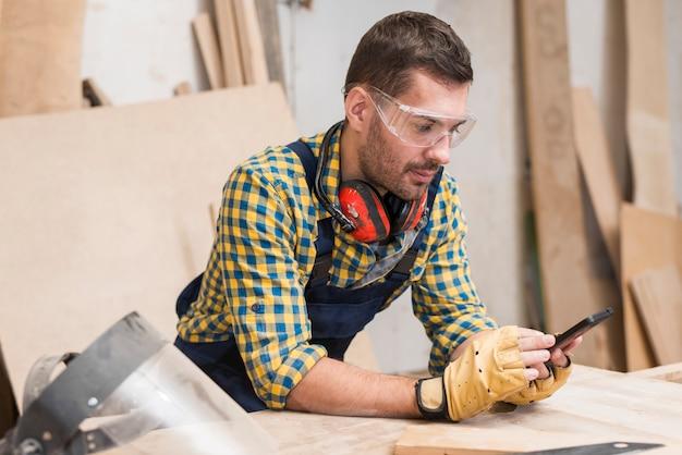 Carpinteiro masculino usando luvas protetoras, olhando para smartphone Foto gratuita
