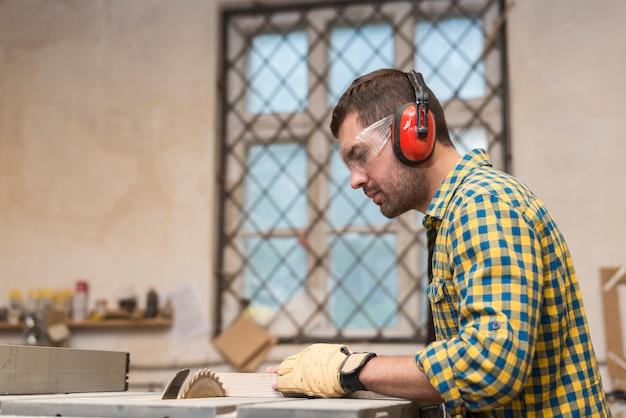 Carpinteiro masculino usando óculos de segurança e defensor de orelha, corte o bloco na lâmina de serra circular Foto gratuita