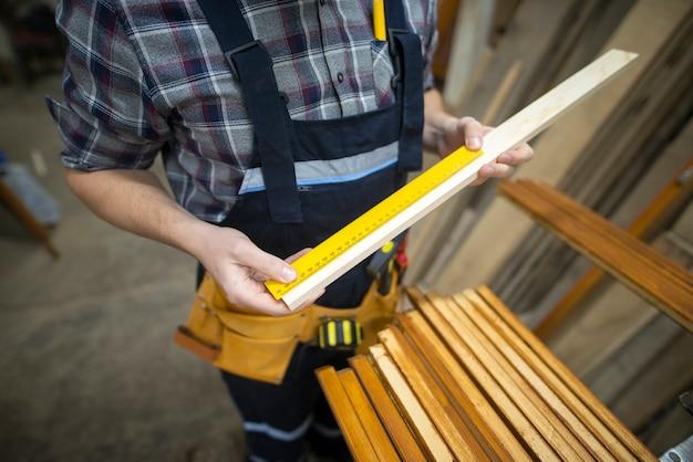 Carpinteiro medindo a prancha que está prestes a cortar na oficina de marcenaria Foto gratuita