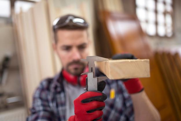 Carpinteiro medindo espessura de material de madeira de prancha com calibre vernier para novo projeto Foto gratuita
